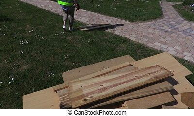 Woman sorting planks at outdoor