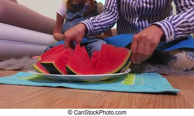 Woman sorting watermelon pieces on dish
