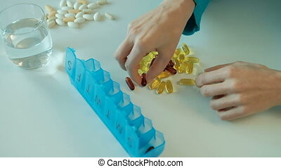 Woman sorts nutritional vitamins in blue tablet box on the week.