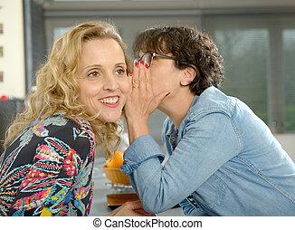 woman speaking in the ear of her friend