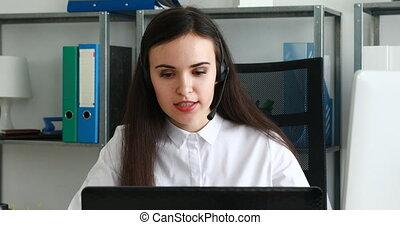 woman speaking on headset in modern office.