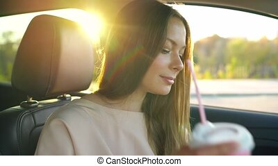 Woman speaks on the smartphone and drinks coffee in the car...