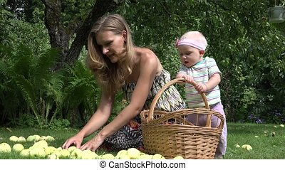 woman spend freetime with baby daughter in park with apple. 4K