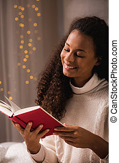 Woman spending winter evening on reading a book