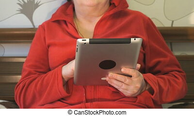 Woman spends free time using a digital tablet. Woman lies on...