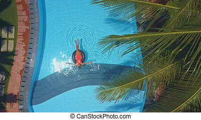 woman spends holiday swimming in pool under palms