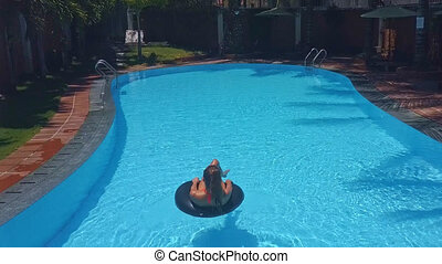 woman spends leisure sunbathing on lifebuoy in pool