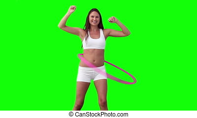 Woman spinning a hula hoop with her arms spread against a...