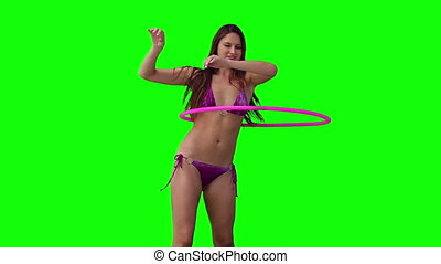 Woman spinning a hula hoop with her arms raised over her...