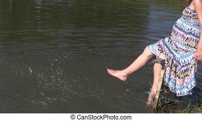 woman splash feet pond