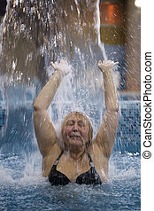 Woman splashing in a pool under jet of water