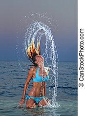 woman splashing in tropical water with white bikini