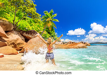 Woman splashing wave Seychelles