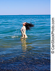 woman splashing wet hear sea