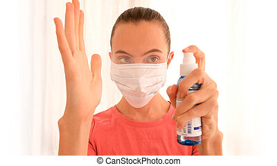 Woman spray her hands with a disinfectant spray on a white background. Coronavirus hand sanitizer sanitiser gel for clean hands hygiene corona virus spread prevention