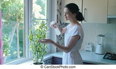 Woman spraying a plant with water