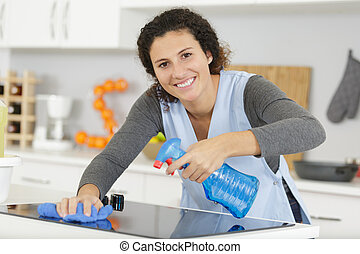 woman spraying houshold cleaner on kitchen counters