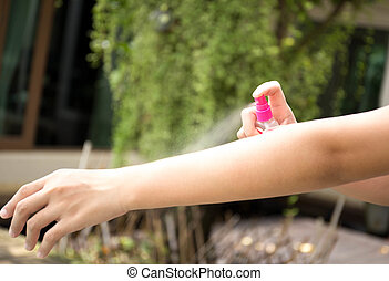 Woman spraying insect repellents on skin in the garden