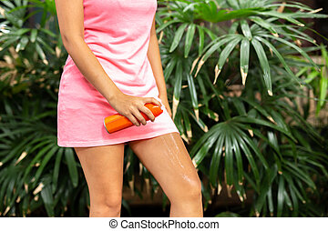 Woman spraying mosquito insect repellent on leg outdoor in nature forest.