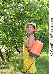 Woman spraying tree branches