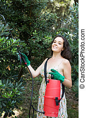 Woman spraying tree in orchard