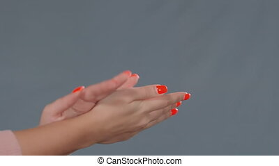 woman sprays antiseptic on hand palm with red manicure