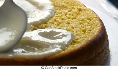 Woman spreading a cream on the baked dough. Female hand pour...