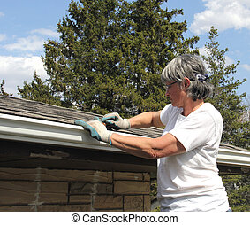 Woman spring cleaning rain gutters