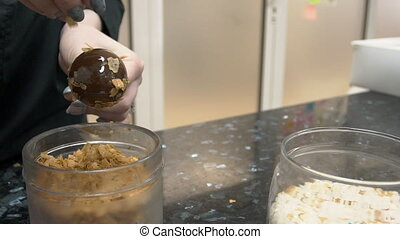 Woman sprinkles chocolate ball with flakes in kitchen...