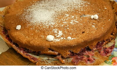 Woman sprinkles with powdered sugar a homemade brown pie - A...