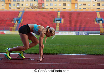 woman sprinter leaving starting blocks on the athletic...