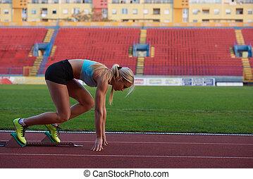 woman sprinter leaving starting blocks on the athletic...