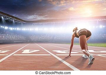 Woman sprinter start ready position on a stadium