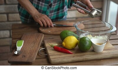 Woman squeeze the garlic for guacamole recipe in kitchen.
