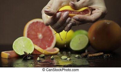 Woman squeezing a fresh and juicy grapefruit with hands....