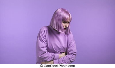 Woman squeezing belly with hands because of abdominal pain. Lady suffering from stomach ache. Healthcare, problem with menstrual period cramps or bowel flatulence concept. High quality 4k
