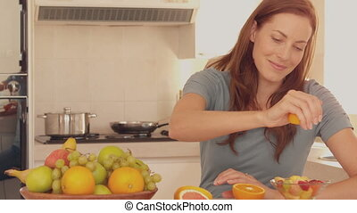 Woman squeezing orange over her fru