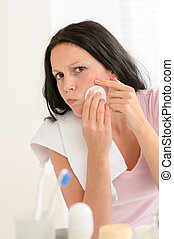 Woman squeezing pimple cleaning acne skin
