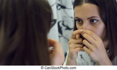 Woman squeezing pimples in a front of the mirror