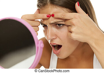woman squeezing pimples - young woman looking at herself in...