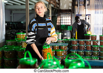 Woman stacking glass jars with pickled olives
