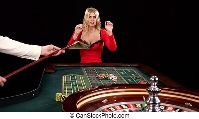 Woman stakes piles of chips playing roulette at the casino. Black