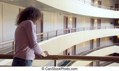Woman stand at balcony with handrail in multiple floor building