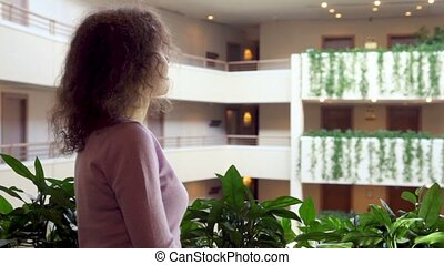 Woman stand at balcony with plants in multiple floor...
