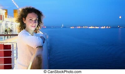 Woman stand on deck near fence and watch seascape during cruise