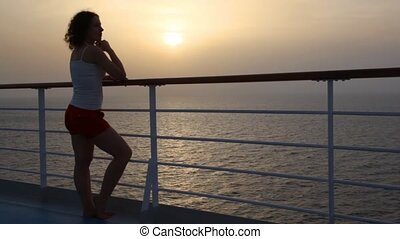 woman stand on deck of cruise ship and looks at sea
