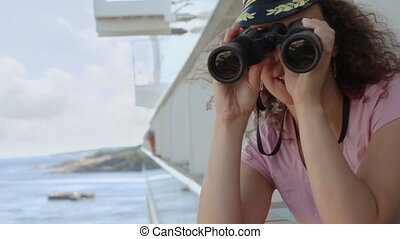 Woman in white marine cap stand on deck with binoculars during cruise