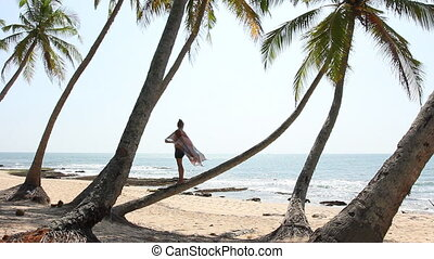 Woman Stand on palm tree.