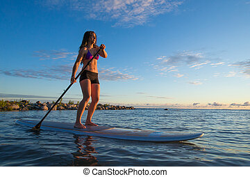 Woman Stand Up Paddle Boarding - A young woman stand up...
