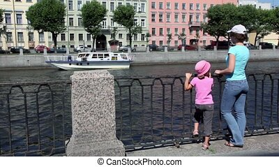 Woman stand with daughter on quay near fence